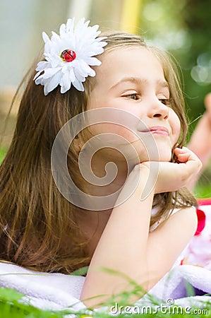 Little girl lying on green grass