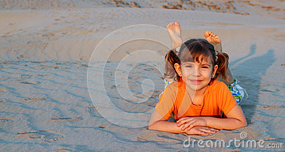 Little girl lying on sand