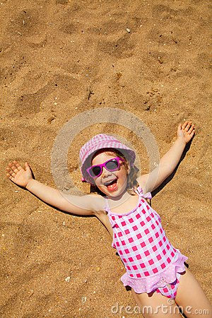 Little girl lying on sandy beach