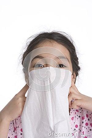 Little girl makes a veil for fun