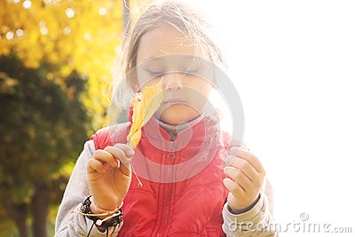 Little girl with maple leaf in  hand