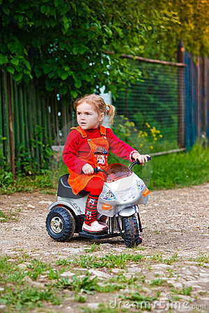 Little girl on the moped in the country