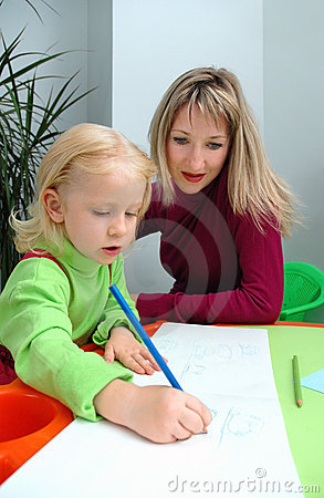 Little girl with mother draws pencil