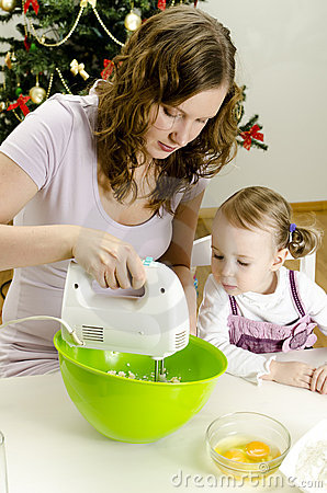 Little girl and mother are preparing cookies