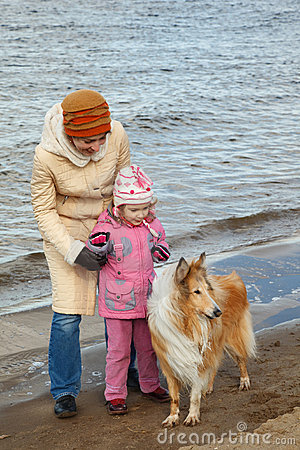 Little girl with mum and dog walk on autumn beach