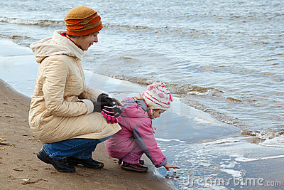 Little girl with mum walk on autumn beach