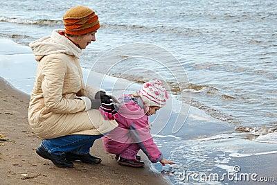 Little girl with mum walk on autumn beach