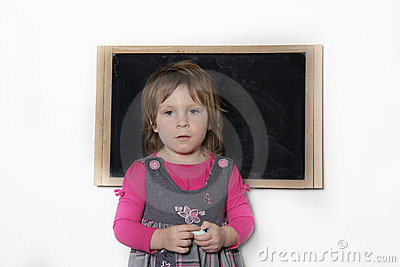 Little girl near blackboard