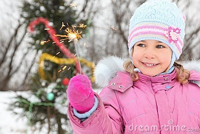 Little girl near christmass tree with bengal light