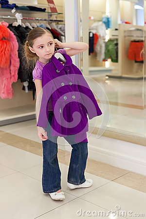Little girl near a mirror try on clothes in store