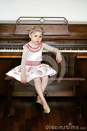 Little girl next to a piano