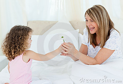 Little girl offering a gift to her grandmother