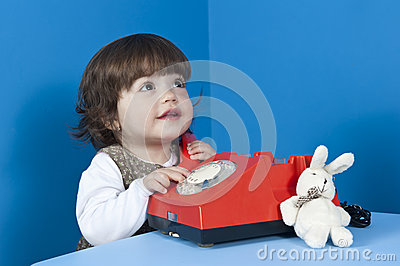 Little girl with old red phone