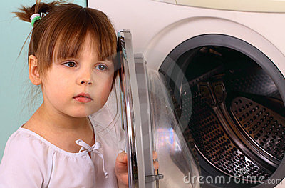 A little girl opens the washing machine