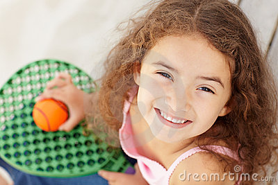 Little girl outdoors holding bat and ball
