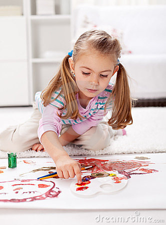 Little girl painting with finger