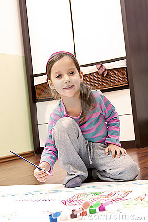 Little girl painting in her room