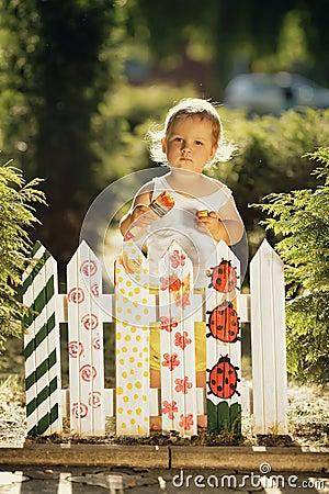 Little girl paints a fence