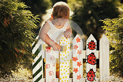 Little girl paints a fence