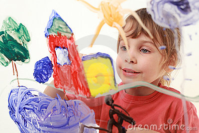 Little girl paints on glass, house, tree