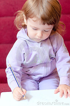 Little girl paints with a pencil.