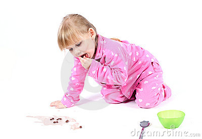 Little girl in pink pyjamas eating cereal