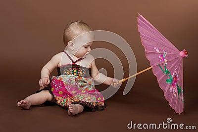 A little girl a pink umbrella