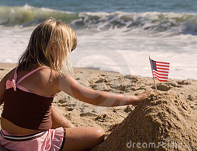 Little Girl planting flag in sand