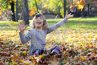 Little girl play with autumn leaves