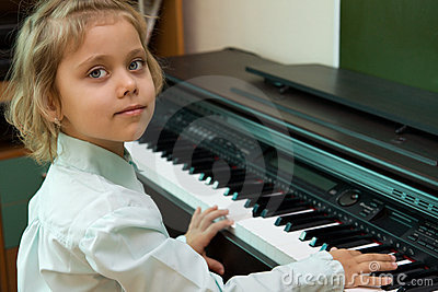 Little girl play on a electric piano