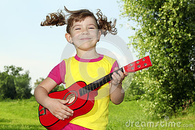Little girl play guitar outdoor
