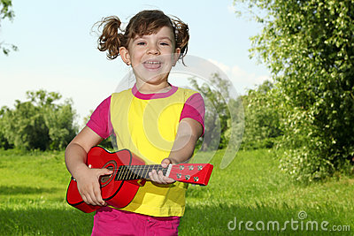 Little girl play guitar and sing
