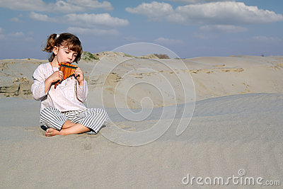 Little girl play panpipe in desert