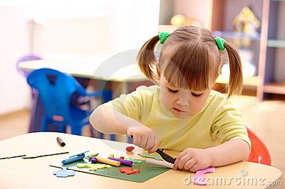 Little girl play with plasticine in preschool