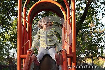 Little girl on playground slide