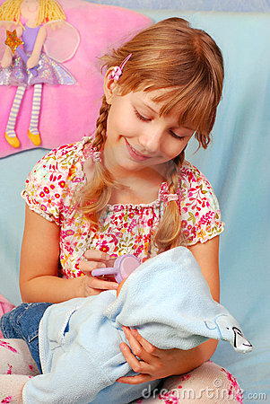 Little girl playing with baby doll