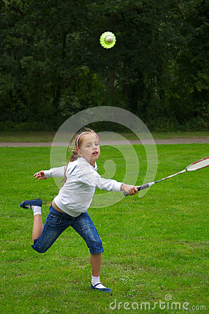 Little girl playing badminton outdoors