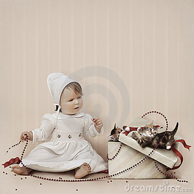 Little girl playing with beads and kittens in a gi