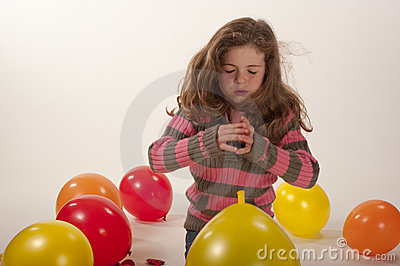 Little girl playing with colorful balloons