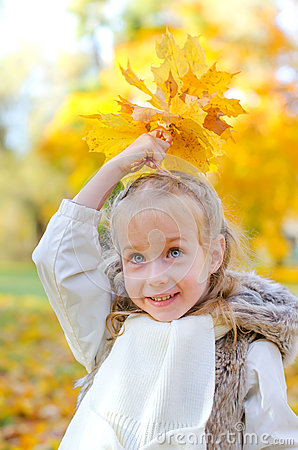Little girl playing with leaves.