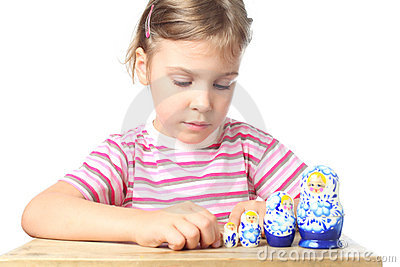 Little girl playing with matryoshka isolated