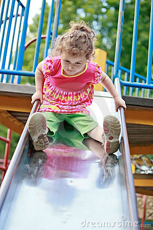 Little girl playing on a playground slide.