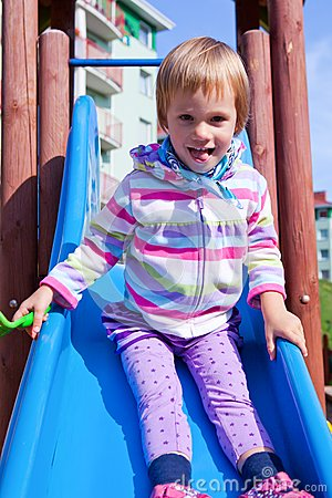 Little girl playing on a playground slide