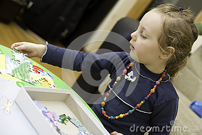 Little girl playing a puzzle game