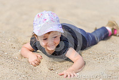Little girl playing in the sand on the beach.