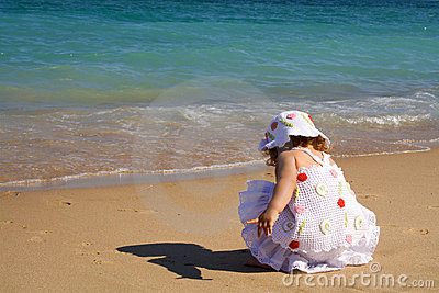 Little girl playing by the sea