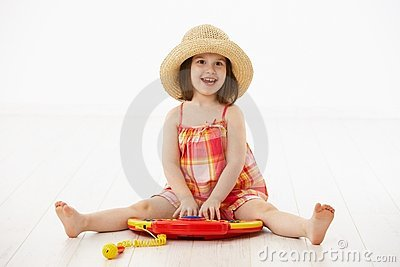 Little girl playing with toy instrument