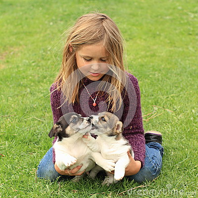Little girl playing with two puppies