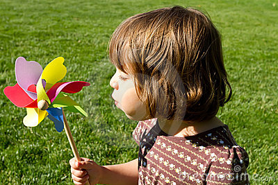 Little girl playing with wind spinner