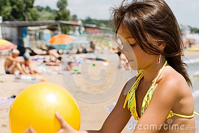 Little girl plays ball at crowded seaside